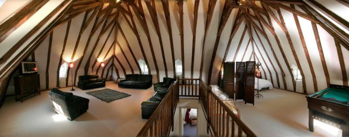 The relax room with its slightly sloping ceilings under an inverted hull shaped roofing framework would make some wonderful bedrooms
